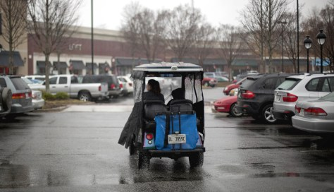 Image: A golf cart driver looks for a parking space in a busy shopping center parking lot in Peachtree City, Ga.