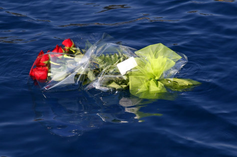 Image: Flowers thrown by family members of missing victims from the Costa Concordia cruise ship which ran aground off the west coast of Italy, float near the Costa Concordia at Giglio island