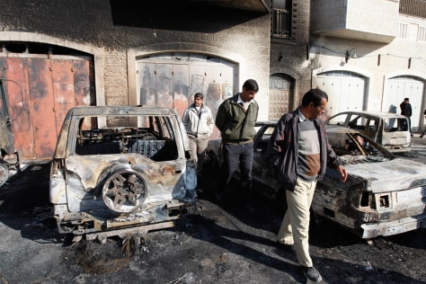 Image: Palestinians inspect cars they say were torched by Jewish extremists