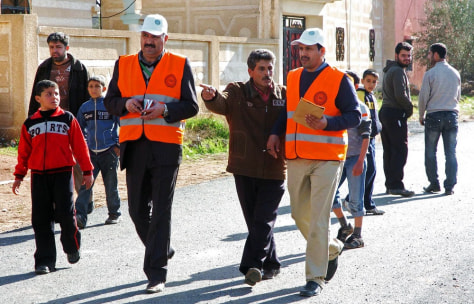 Image: Arab League observers tour the town of Mseifrah in Syria's southern Daraa province on January 5,