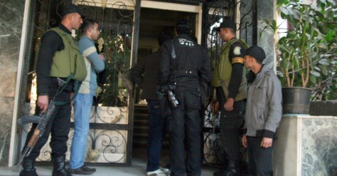 Image: Egyptian military stand guard as officials raid a non-governmental organization offices in Cairo.