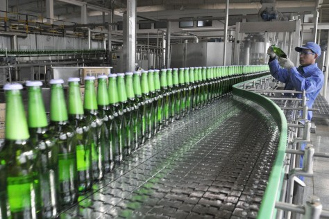 Image: beer on a production line at the Tsingtao brewery in Rizhao, Shandong province, China
