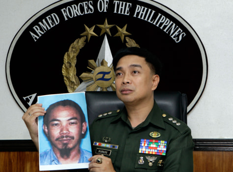 Image: Armed Forces of the Philippines spokesman Col. Marcelo Burgos shows a picture of Malaysian Zulkipli bin Hir, also known as Marwan, a top leader of the regional, al Qaida-linked Jemaah Islamiyah terror network
