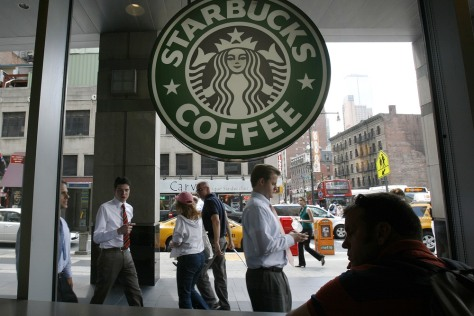 Image: File photo of people walking past the Starbucks outlet on 47th and 8th Avenue in New York