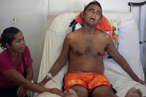 Image: Segundo Zapata Palacios rests in a hospital as his wife Emma Vanegas sits at his bedside