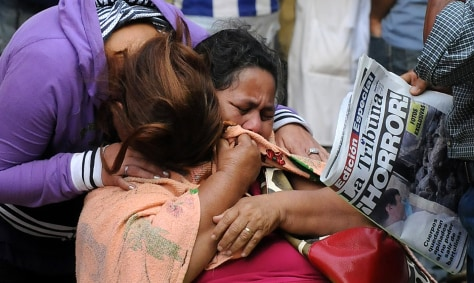 Image: Women cry while they wait to recover the remains of a relative, killed during Comayagua prison fire, at the Forensic Department in Tegucigalpa.