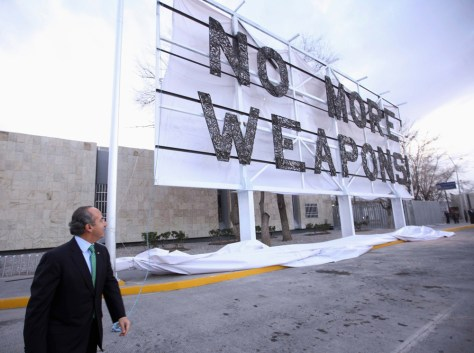 "Image: Mexican President Felipe Calderon and ""No More Weapons!"" billboard"