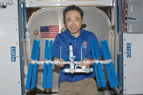 astronaut holds LEGO ISS model