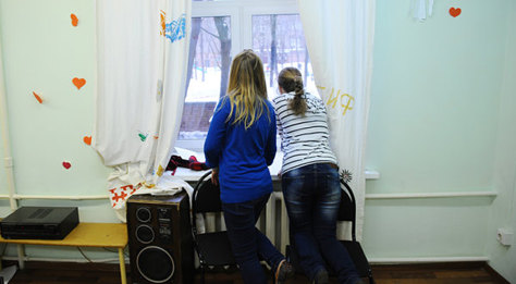 Two girls look out the window at a center in Moscow that offers psychological help to teenagers. Experts say more like it are needed.