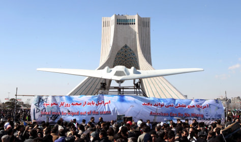 Image: Iranians gathered around a replica of an US RQ-170 drone