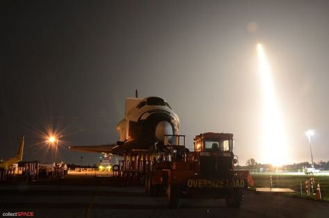 Falcon rocket launches behind shuttle mockup