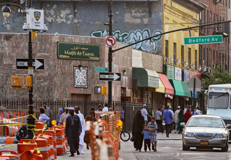 Image: people pass below a New York Police security camera, upper left, situated above a mosque on Fulton St., in the Brooklyn neighborhood of Bedford-Stuyvesant in New York