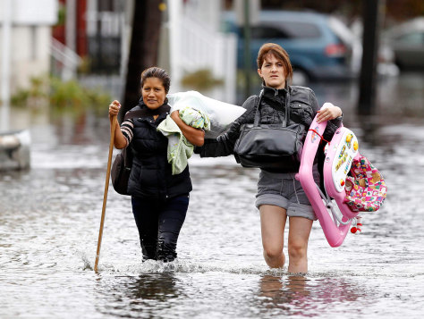 Image: Residents make their way through flood waters brought on by Hurricane Sandy in Little Ferry, NJ