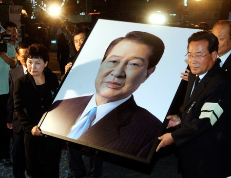Image: South Koreans carry a portrait of the late former South Korean President Kim Dae-Jung
