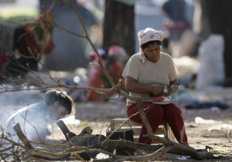 Image: A family cooks a meal in a city square where they are living under a makeshift tent in downtown Asuncion