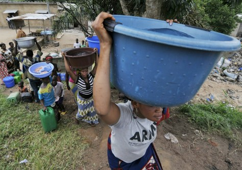 Image: Women carry tubs of water on their heads
