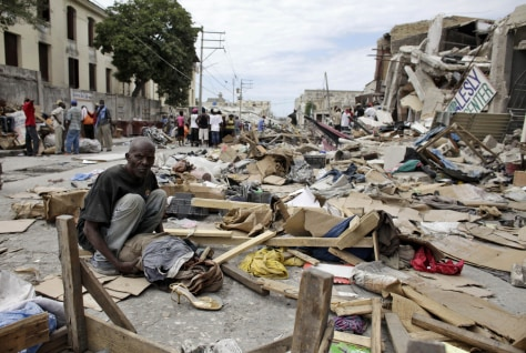 Image: A resident sits at a destroyed area after a major earthquake hit the capital Port-au-Prince