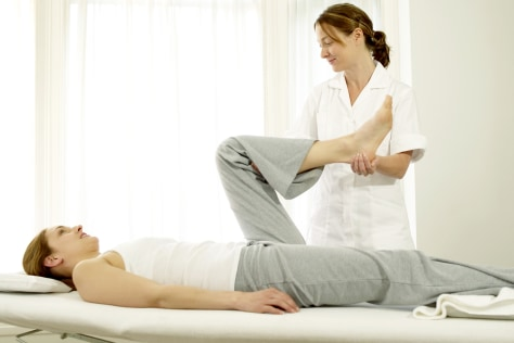 Image: Physical therapist works with patient.