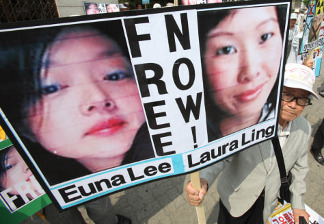 Image: South Korean protester with photos of American journalists