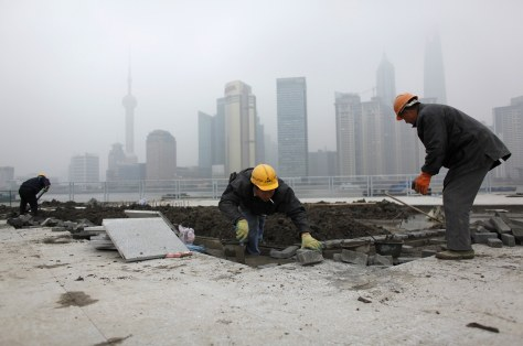 Image: Migrant labourers work at a construction site near The Bund on the banks of the Huangpu River in Shanghai