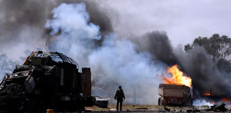 Image: A rebel fighter looks at burning vehicles after a coalition air strike