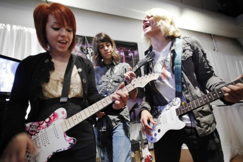 Image: Carly Kalafus, left, Ben Spremulli, center, and Duran Visek perform on Paper Jamz guitars
