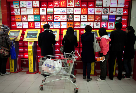 Image: People use a row of coupon machines near a supermarket entrance in Beijing, China.