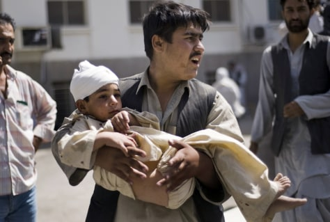 Image: Afghan man carries a wounded child in Kabul