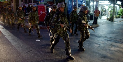 Image: Thai soldiers in riot gear patrol the streets around the 'Red Shirt' fortified camp in downtown Bangkok
