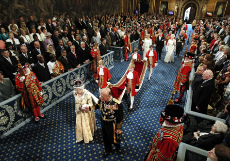 Image: Britain's Queen Elizabeth and Prince Philip walk through the Royal Gallery in the Palace of Westminster