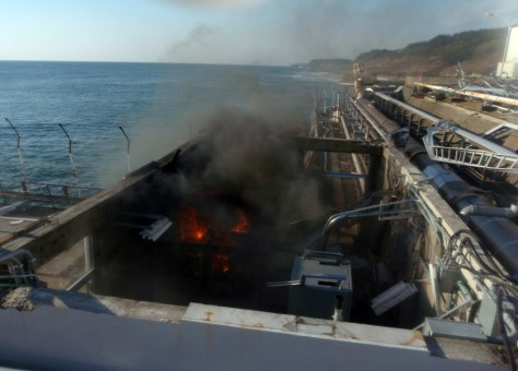 Image: Fire and smoke are seen at a building for sampling from seawater near No.4 reactor of the Tokyo Electric Power Co.'s Fukushima Dai-ichi Nuclear Power Plant