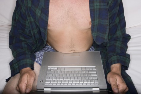 Image: Image: man in his underwear using a laptop on the couch