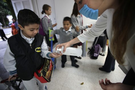 Image: school official hands out antibacterial gel