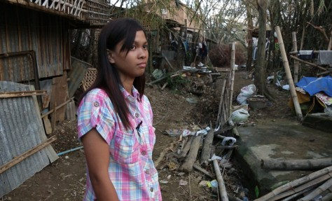 Image: 20-year-old Queennie Lucio stands among the wreckage from Typhoon Haiyan near her home in Estancia, Philippines.