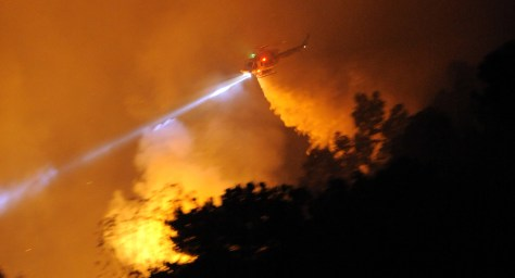 Image: A helicopter douses a wildfire in Calif.