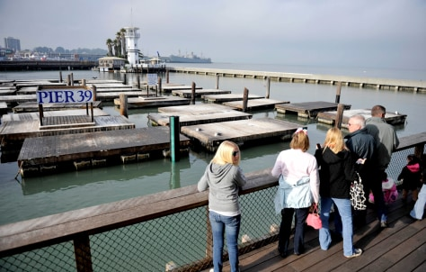 Image: Tourists look at Pier 39 where sea lions used to abound