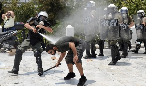 Image: A protester clashes with riot police in Athens.