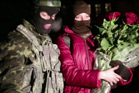 Image: A protester stands next to his girlfriend after proposing to her in a street close to Kiev's Independence Square