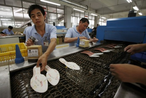 Image: Workers make soles at a shoe factory in Ganzhou, Jiangxi province