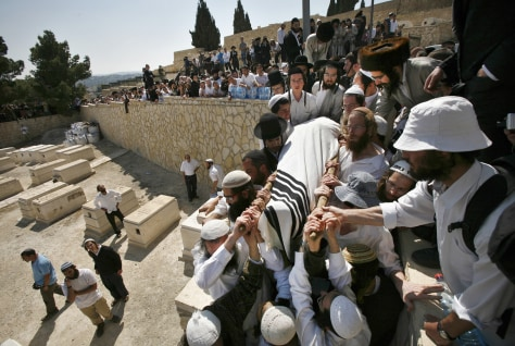 Image: People carry the body of Ben-Yosef Livnat during his funeral at Mount of Olives cemetery in Jerusalem