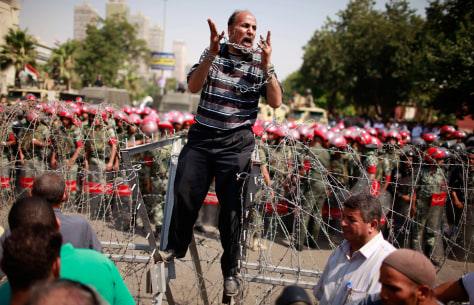Image: Protester shouts as he stands on top of a barricade in front of soldiers outside the Supreme Constitutional Court in Cairo