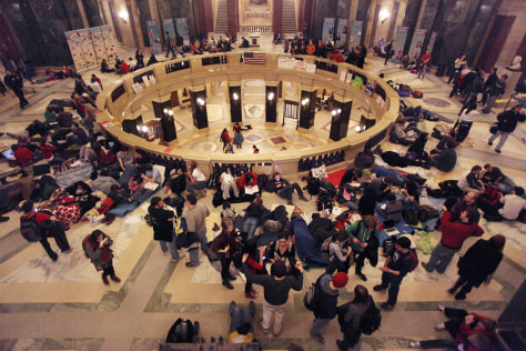 Image: People put down sleeping bags and blankets for an all-night vigil at the Capitol in Madison, Wis. near midnight
