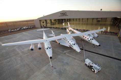 "Image: Virgin Galactic's first SpaceShipTwo suborbital spaceliner (center) is seen mated to its WhiteKnightTwo mothership in front of the ""Faith"" hangar at The Spaceship Company during a dedication ceremony in Mojave, Calif."