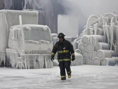 Image: Chicago Fire Department Lieutenant De Jesus walks around an ice-covered warehouse that caught fire Tuesday night in Chicago.