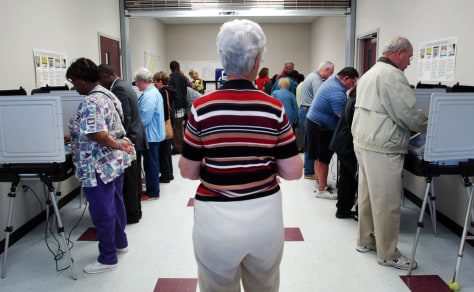 Image: A Board of Elections volunteer watches people cast their ballots