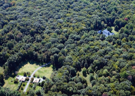 Aerial view of New Canaan showing two caretaker houses and woods