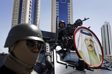 Image: Bahraini soldiers with the portrait of Bahrain's King Hamad bin Isa Al Khalifa, on the armored personnel carrier, are seen at a checkpoint near Pearl Square in Manama