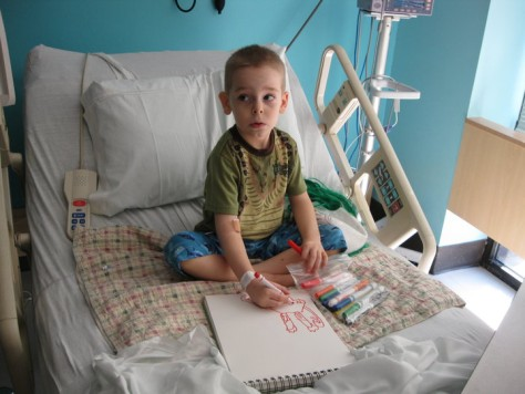 Image: Aidan Reed drawing monster pictures in hospital bed