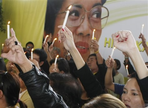 Image: Supporters light candles in front of a portrait of the late Philippine President Corazon Aquino