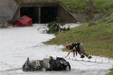 Image: Fireman checks car after flood